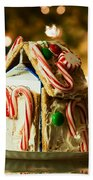 Gingerbread House Against A Background Of Christmas Tree Lights Beach Towel