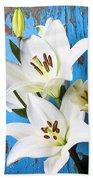 Lilies Against Blue Wall Beach Towel