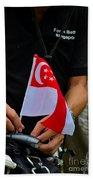 Man Plants Singapore Flag On Bicycle Beach Towel