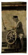 old sailor A vintage processed photo of a sailor sitted behind the rudder in Mediterranean sailing Beach Towel