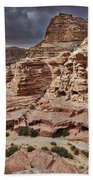 rock landscape with simple tombs in Petra Beach Towel