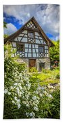 Swiss Chalet In The Garden Beach Towel by Debra and Dave Vanderlaan