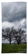 Two Trees Beneath A Dark Cloudy Sky Beach Towel