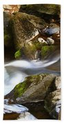 Flowing River Blurred Through Rocks Beach Towel