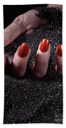 Woman Hand With Red Nails On Black Sand Beach Towel