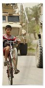 An Iraqi Boy Rides His Bike Past A U.s Beach Towel by Stocktrek Images