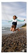 Girl Jumping At Lake Superior Shore Beach Towel