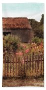 Hollyhocks And Thatched Roof Barn Beach Towel