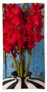 Red Glads Against Blue Wall Beach Towel