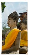 Two Buddha Statues Wrapped In An Orange Scarf  Beach Towel