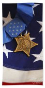 The Medal Of Honor Rests On A Flag Beach Towel