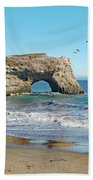 Arch In The Sea With Pelicans Flying By, At Natural Bridges State Beach, Santa Cruz, California Beach Towel
