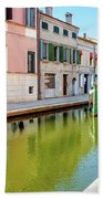 boat in a canal of the colorful italian village of Comacchio in  Beach Towel