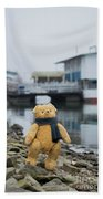 Cheerful Teddy Bear In Knitted Scarf Stand By The Riverside Beside The Port Beach Towel