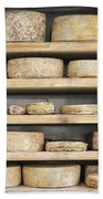 Cheese Wheels On Wooden Shelves In The Cheese Store Beach Towel
