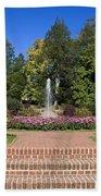 Fountain Among Flowers Beach Towel