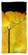 Realistic Orange Fire Explosion Behind Restricted Area Barbed Wire Fence, Blurred Background Beach Towel
