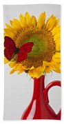 Red Butterfly On Sunflower On Red Pitcher Beach Towel by Garry Gay