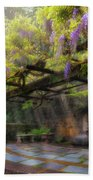 Wisteria Flowers Blooming On Trellis Over Water Fountain Beach Towel