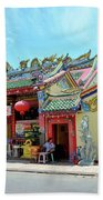 Woman Sits Outside Chinese Temple With Urn And Deity Statues Pattani Thailand Beach Towel