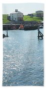 sunlight glistening on water at Eyemouth harbour Beach Towel