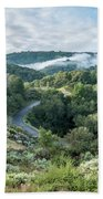 View Of Curved Road Through Dense Forest Area With Low Clouds Ov Beach Towel