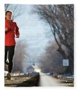 A Woman Running Near A Railroad Track Fleece Blanket