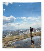 A Backpacker Stands Atop A Mountain Fleece Blanket