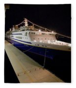 A Cruise Ship At Night Docked Fleece Blanket