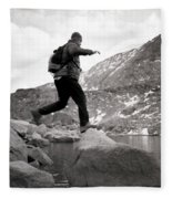 A Man Jumps From One Rock To Another Fleece Blanket