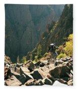 A Man Navigates A Rock Scree Field Fleece Blanket