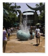 A Water Fountain With Dinosaur Eggs In Universal Studios Singapore Fleece Blanket