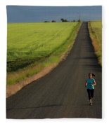 A Woman Running On A Dirt Road Fleece Blanket