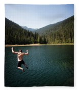 A Young Man Jumps From A Ledge Fleece Blanket