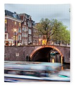 Canal Bridge And Boat Tour In Amsterdam At Evening Fleece Blanket