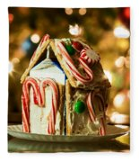 Gingerbread House Against A Background Of Christmas Tree Lights Fleece Blanket