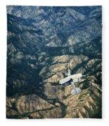 Small Plane Flying Over Mountains Fleece Blanket