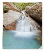 Small Waterfall Casdcading Over Rocks In Blue Pond Fleece Blanket