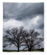 Two Trees Beneath A Dark Cloudy Sky Fleece Blanket