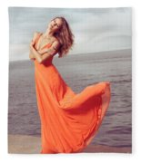 Young Woman In Orange Dress Flying In The Wind At Sea Shore Fleece Blanket