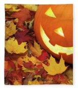 Carved Pumpkin On Fallen Leaves Fleece Blanket
