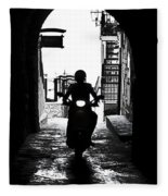 a scooter rider in the back light in a narrow street in Italy Fleece Blanket