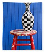 Blach And White Vase On Stool Against Blue Wall Fleece Blanket