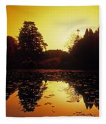 Silhouetted Home And Trees Near Water Fleece Blanket