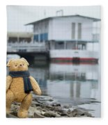 Cheerful Teddy Bear In Knitted Scarf Stand By The Riverside Beside The Port Fleece Blanket