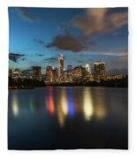 Clouds Roll Over The Austin Skyline As The Neon Reflects In The Glass-like Waters Of Lady Bird Lake Fleece Blanket
