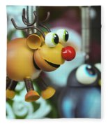 A Rudolph The Red Nosed Reindeer Ornament With A Penguin Fleece Blanket