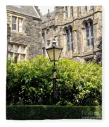 Lamppost In Front Of Green Bushes And Old Walls. Fleece Blanket