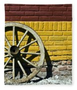 Old Wooden Wheel Against A Wall Fleece Blanket