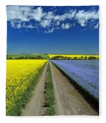 Road Through Flowering Flax And Canola Fleece Blanket